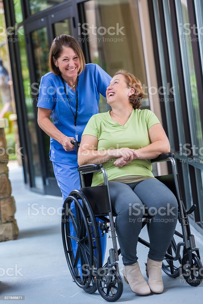 Happy nurse pushing patient in wheelchair after hospital discharge stock photo