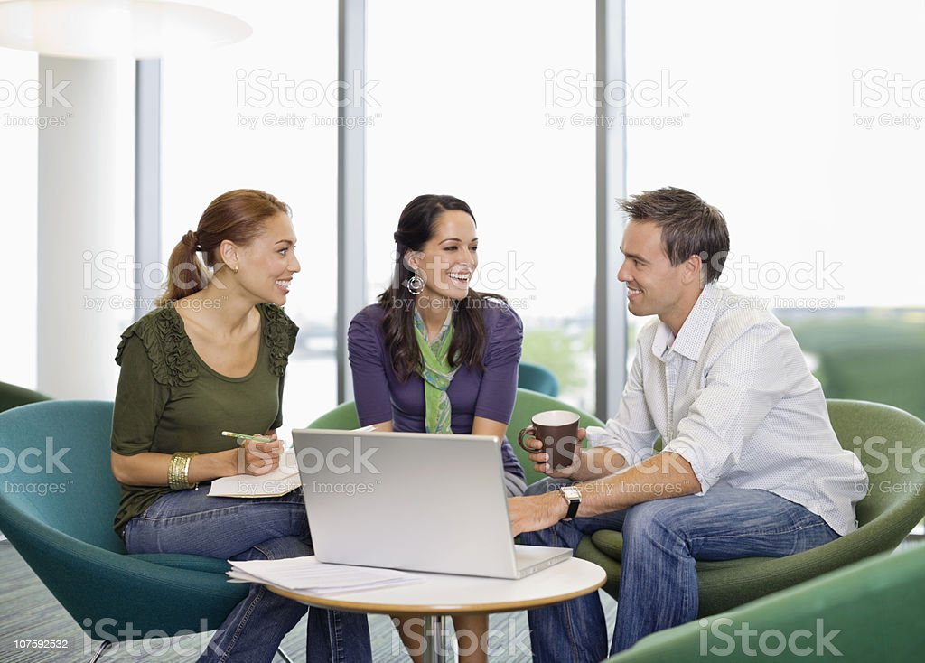 Happy office colleagues sitting at office canteen with laptop royalty-free stock photo