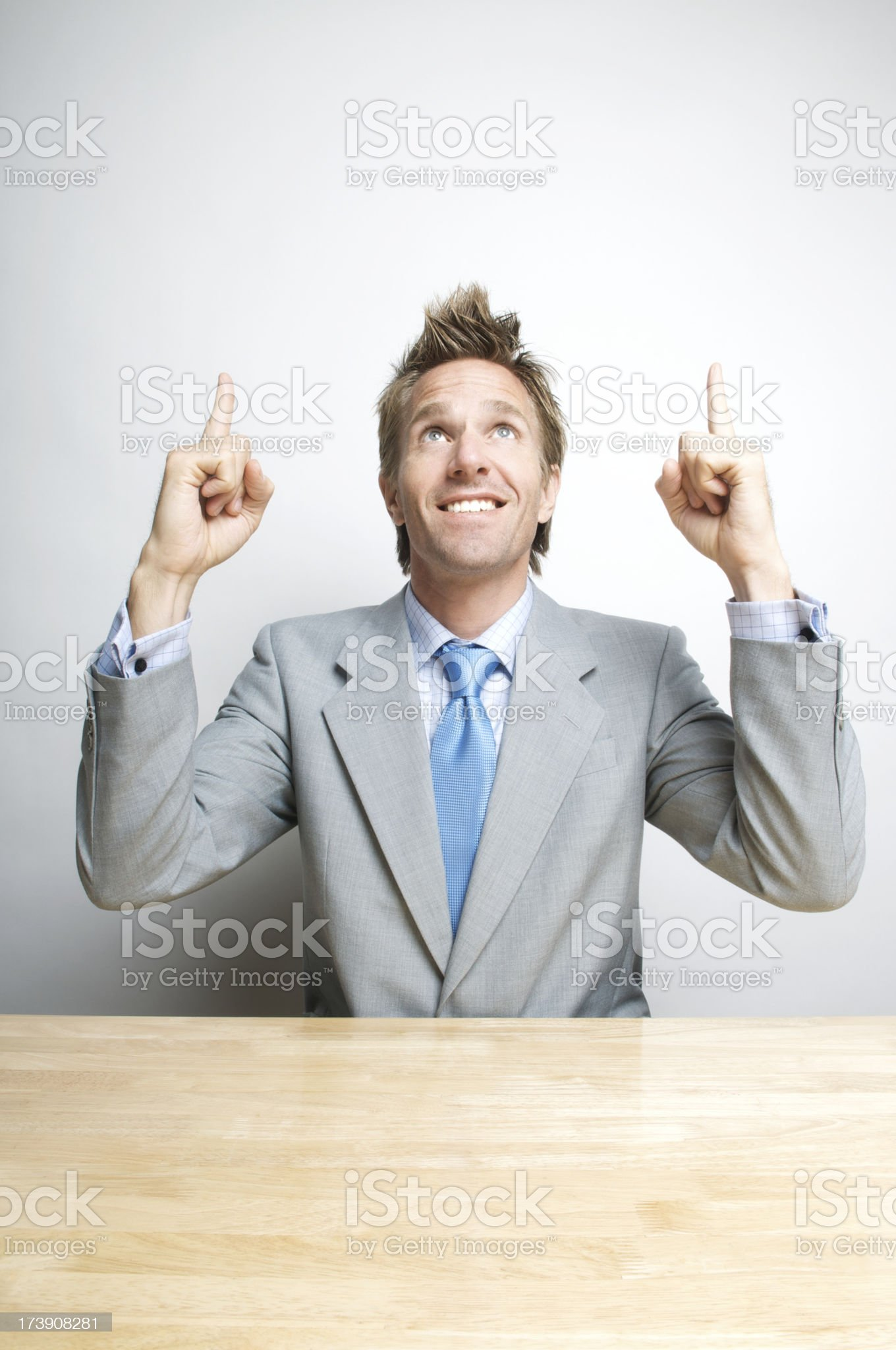 Happy Office Worker Businessman Pointing to Copy Space at Desk royalty-free stock photo
