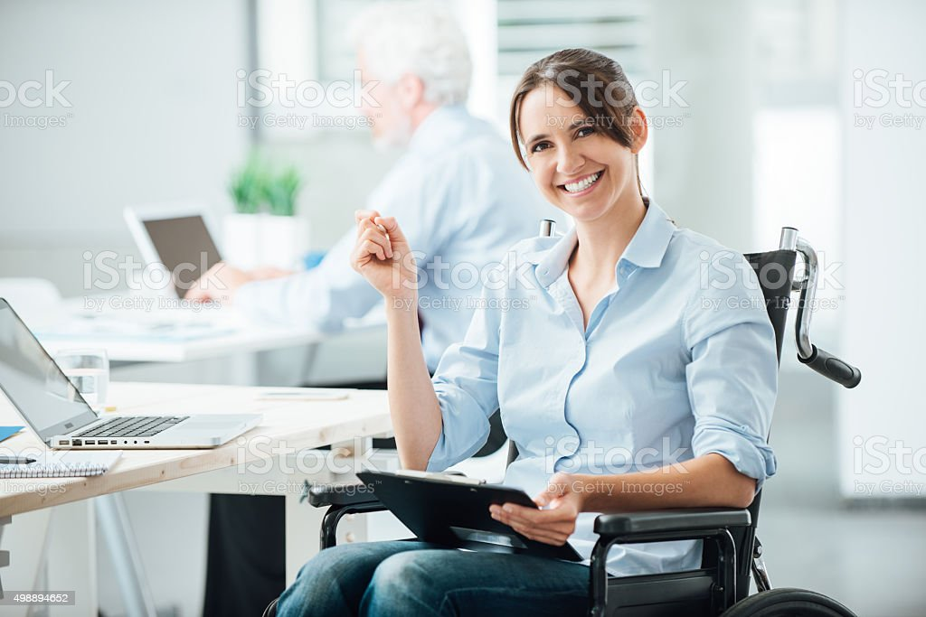 Happy office worker in wheelchair stock photo