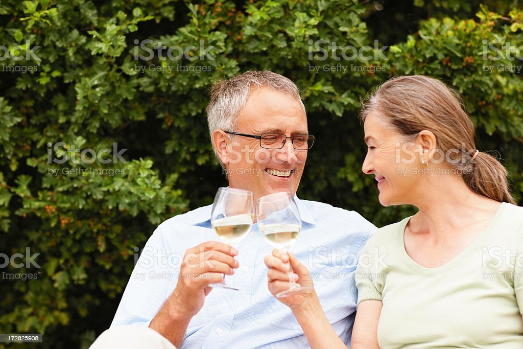 Happy old couple having a glass of champagne while outdoors stock photo
