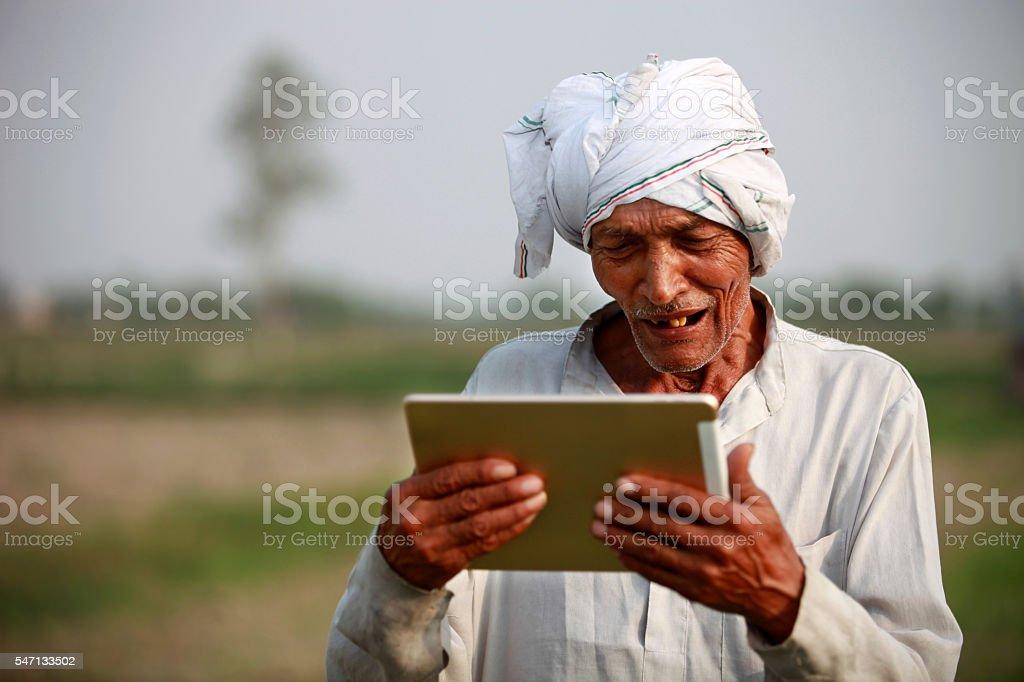 Happy  Old farmer holding digital tablet stock photo