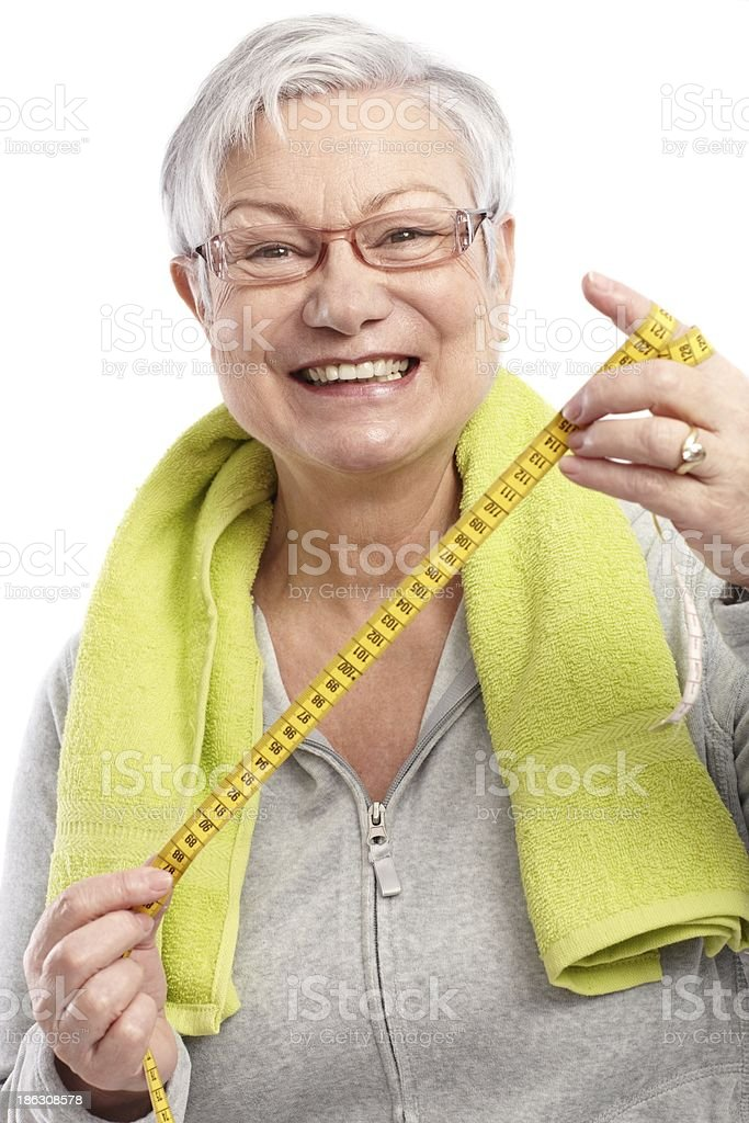 Happy old lady with tape measure stock photo