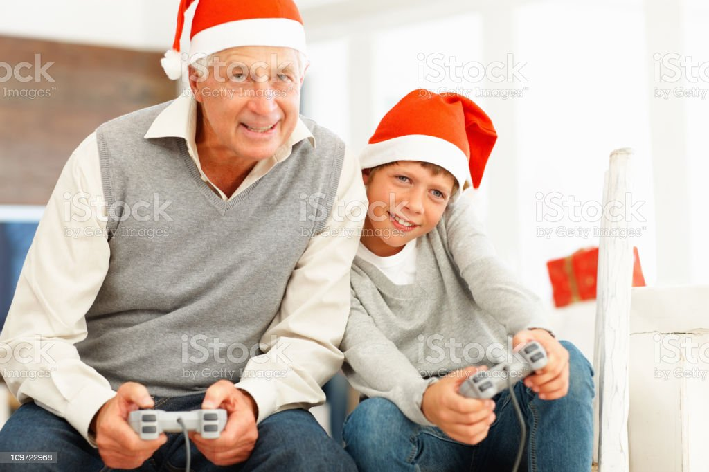 Happy old man playing video game with gradson royalty-free stock photo