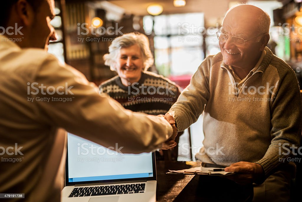Happy old people come to an agreement with insurance agent. stock photo
