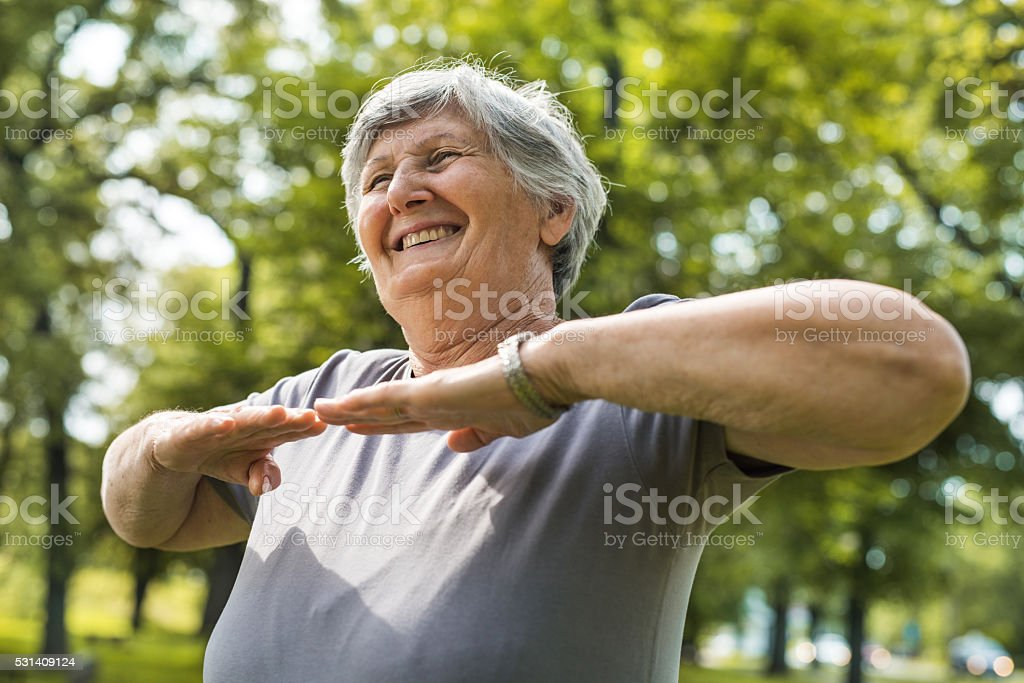 Happy old woman exercising in the park. stock photo
