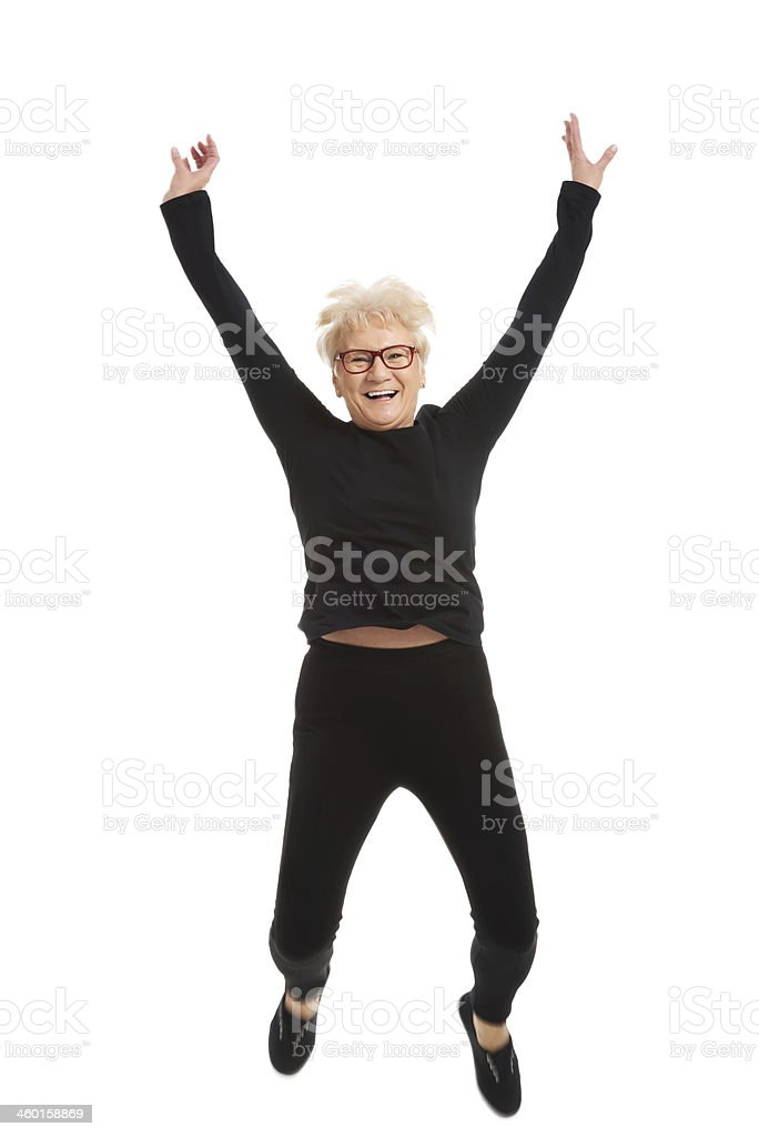 Happy old woman jumping. stock photo