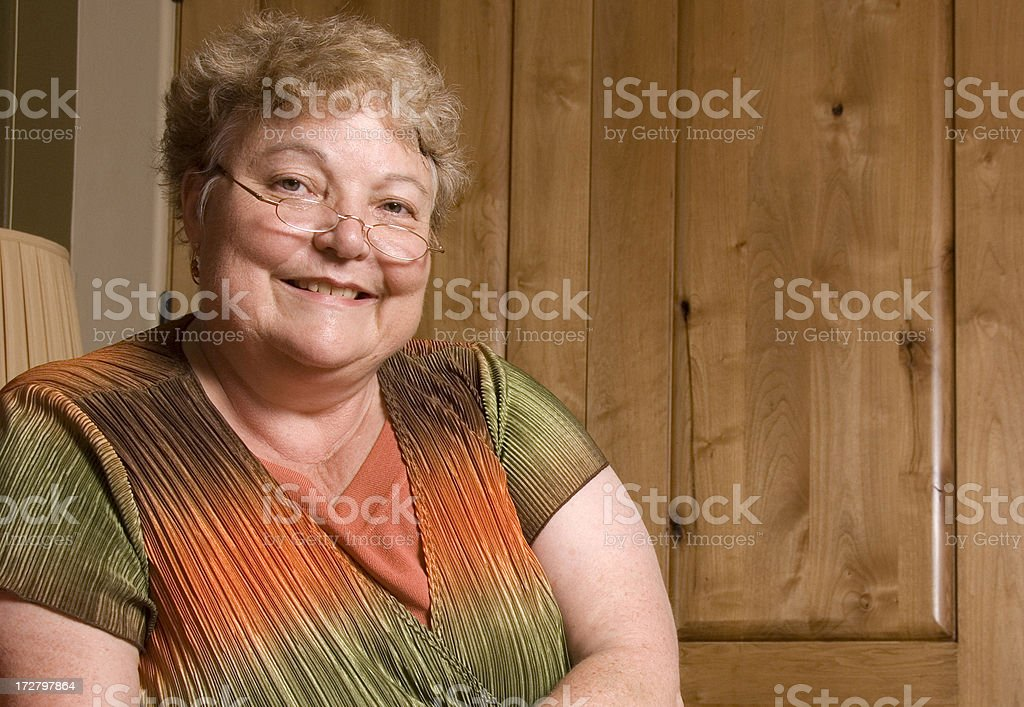 A happy old woman with glasses smiling stock photo