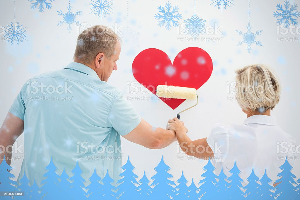 Happy older couple painting red heart stock photo