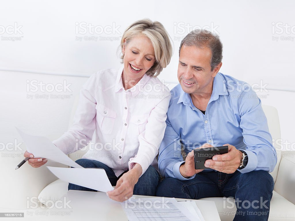 Happy older couple reviewing finances stock photo
