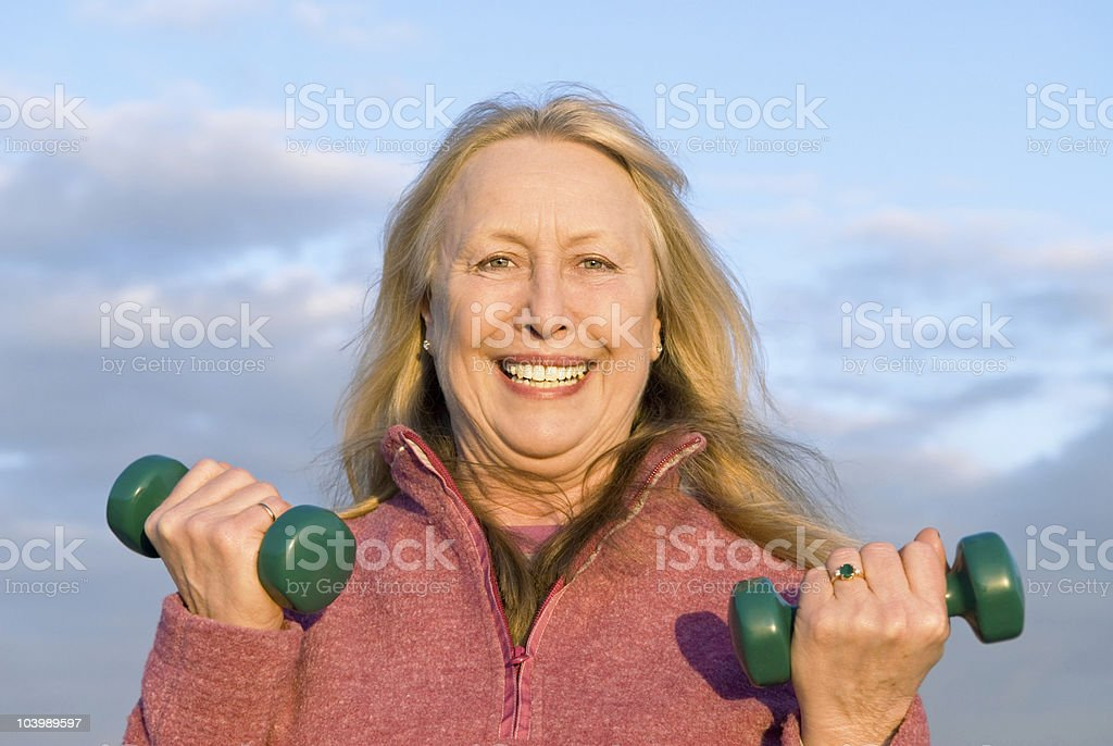 happy older woman exercising with dummbells royalty-free stock photo