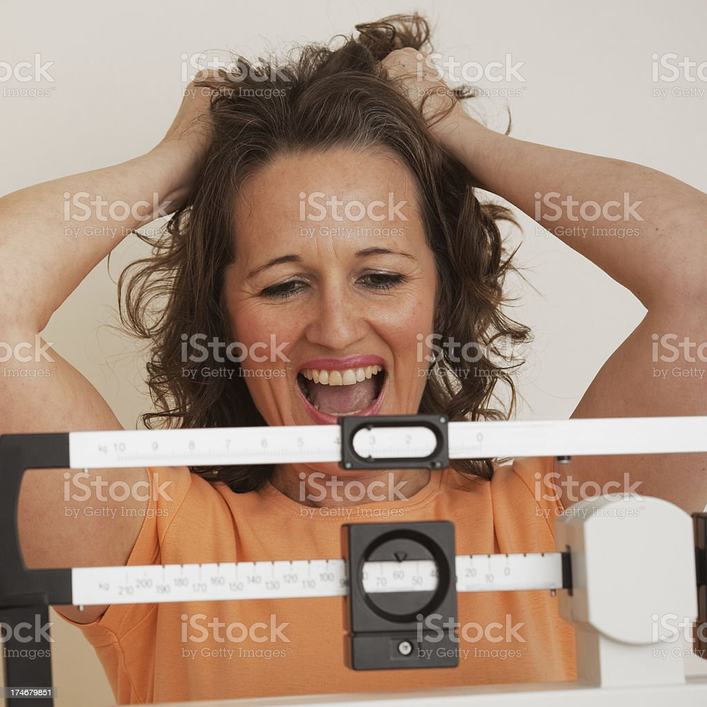 Happy on the weight scale royalty-free stock photo