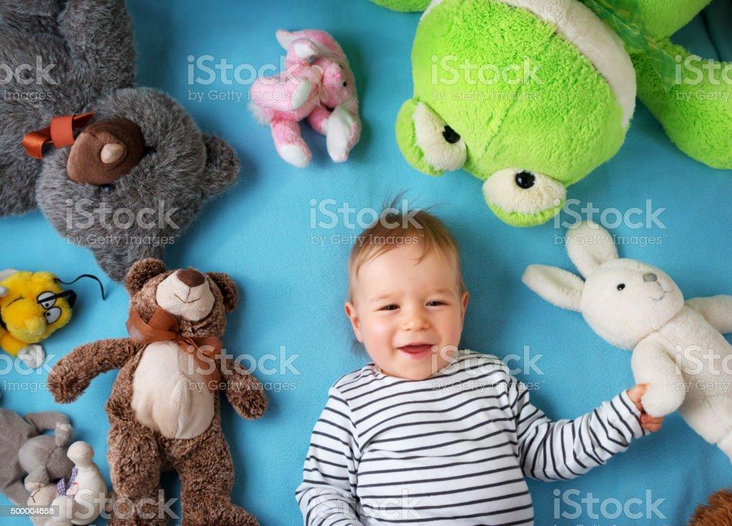 Happy one year old boy lying with many plush toys stock photo