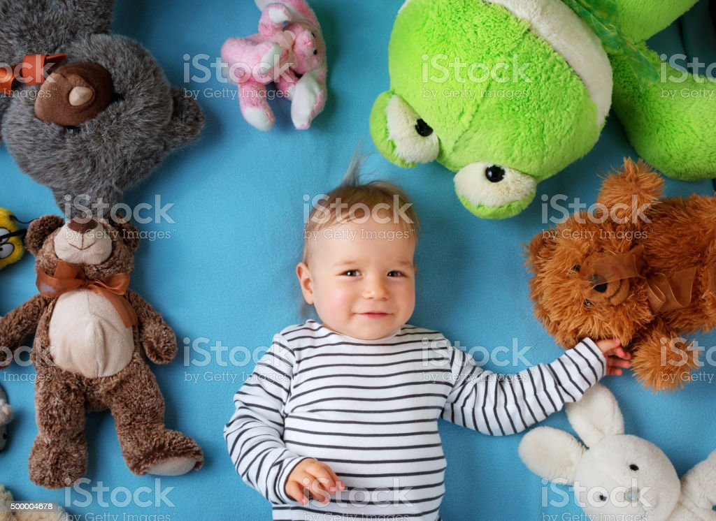 Happy one year old boy lying with many plush toys stock photo