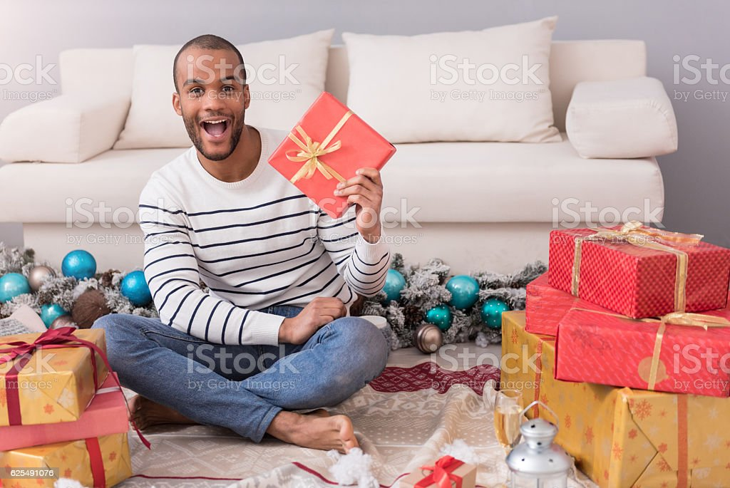 Happy optimistic man holding his present stock photo