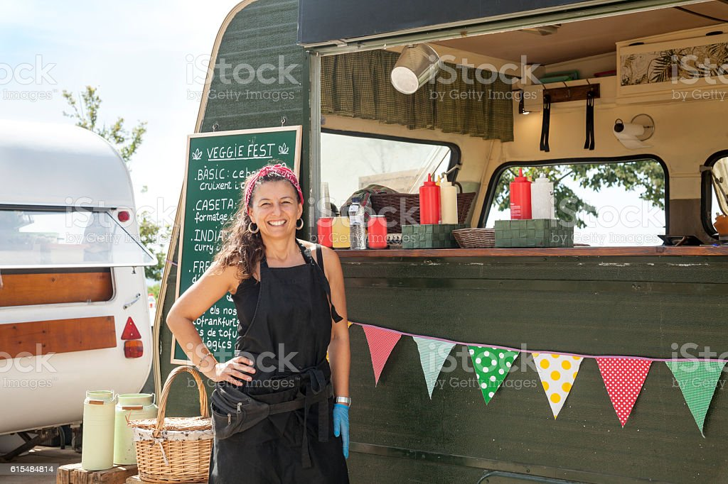 Happy owner woman and her food truck stock photo