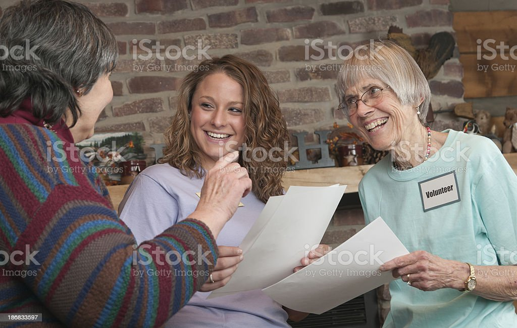Happy Pair of Volunteer Women Receive Instruction from Leader royalty-free stock photo