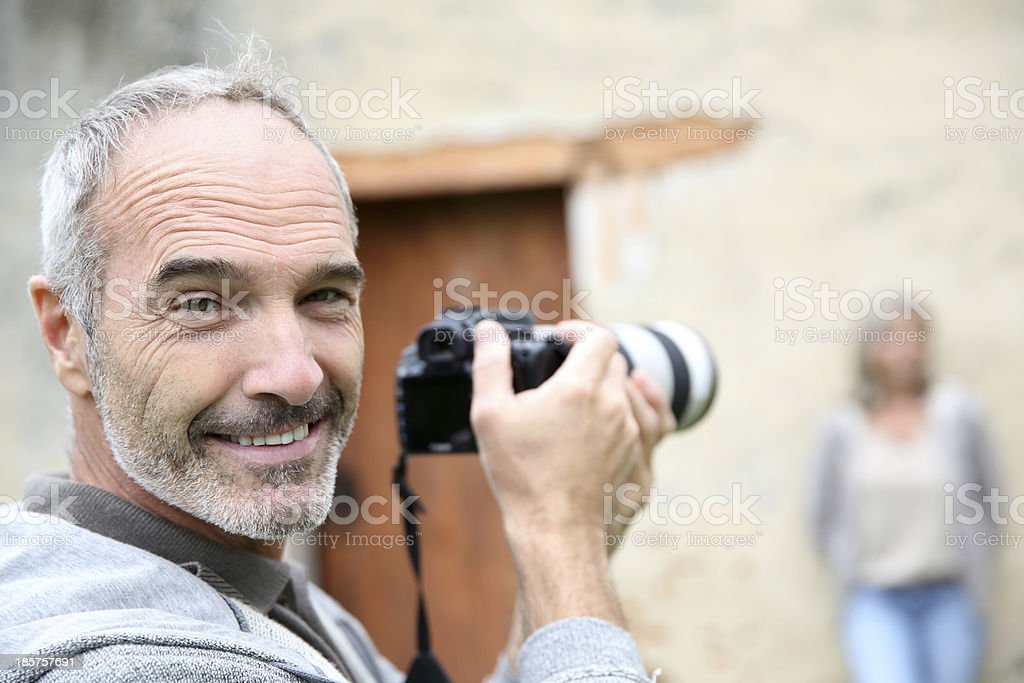 Happy paparazzi photographer taking pictures of woman royalty-free stock photo