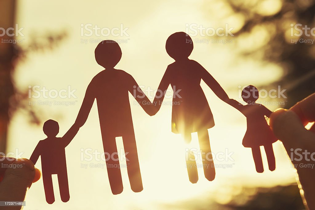 Happy paper dolls family in human hand stock photo