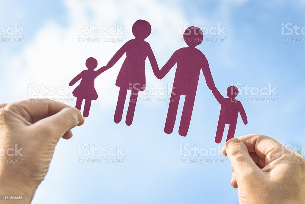 Happy paper dolls family in human hand royalty-free stock photo