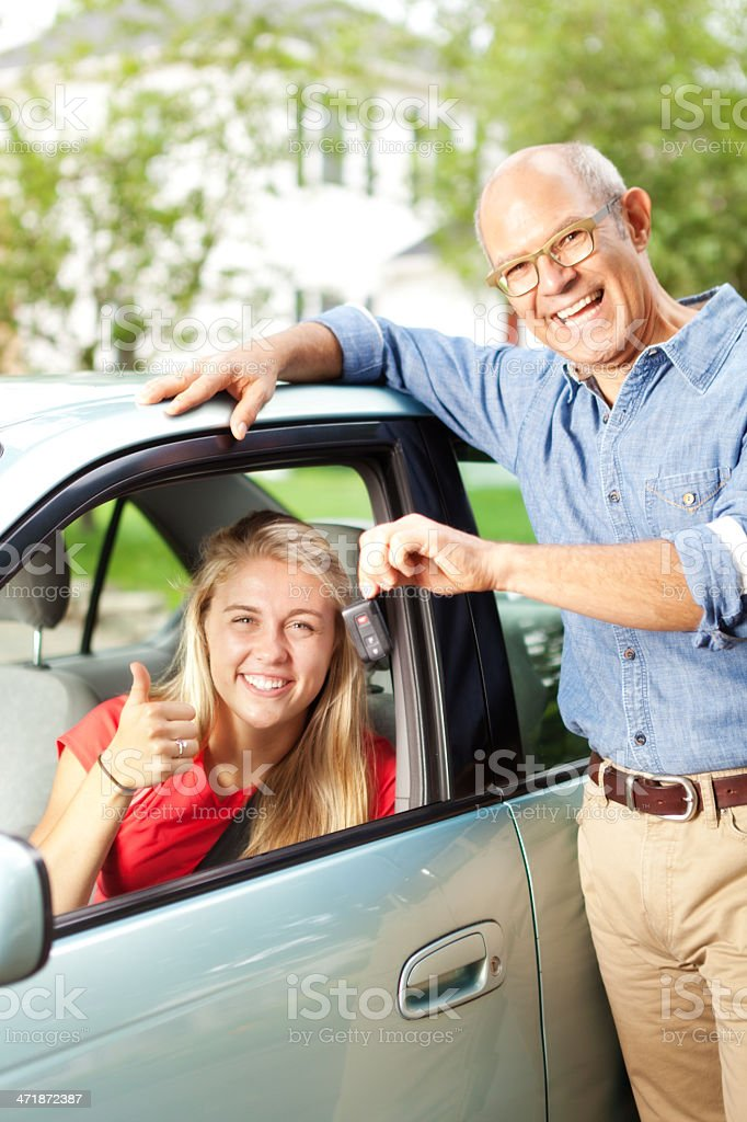 Happy Parent Handing Car Key to Teen Driver Vertical royalty-free stock photo