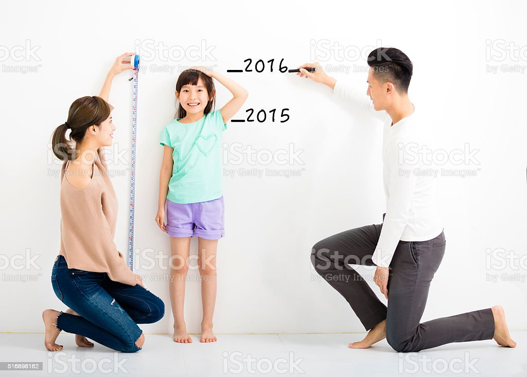 happy parent measures the growth of   daughter stock photo