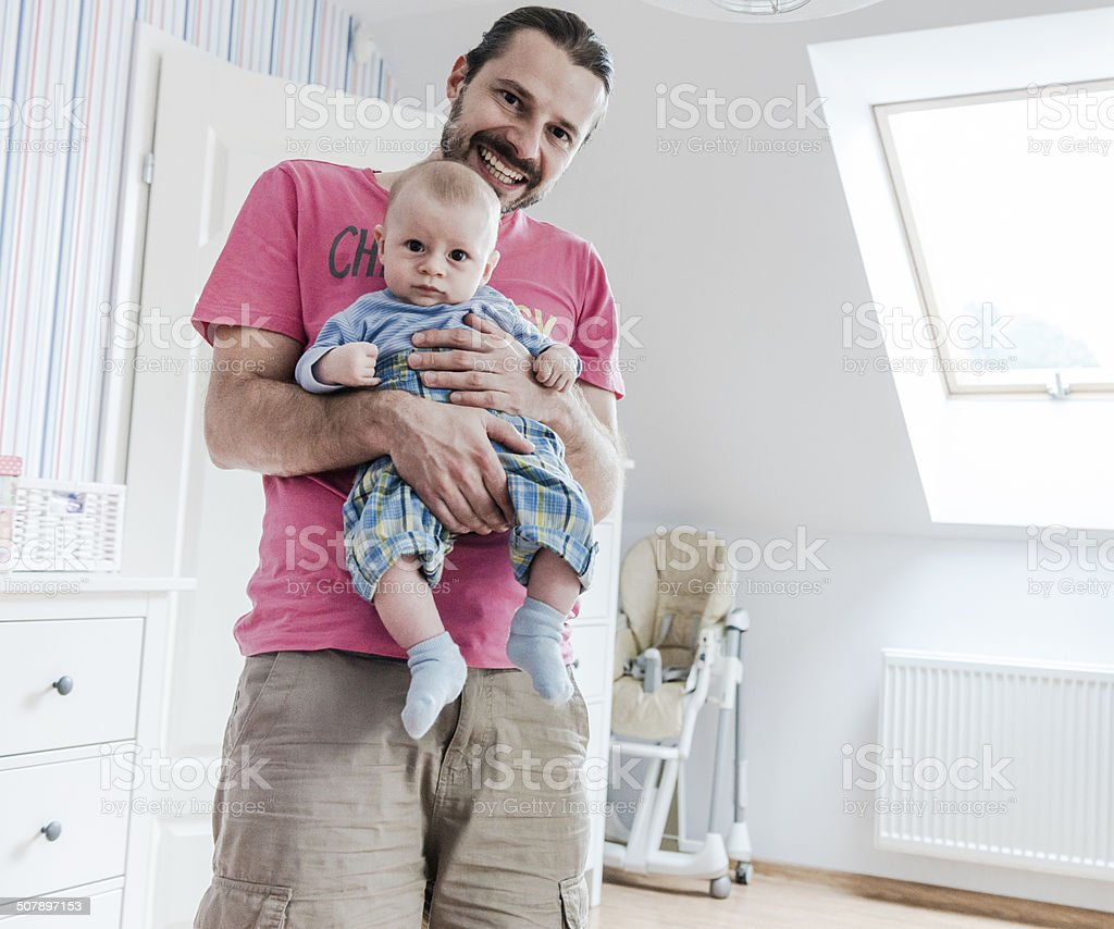 Happy parenting, single father with baby on hands, home interior stock photo