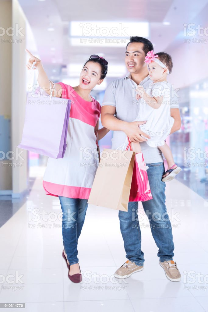 Happy parents and child pointing something stock photo