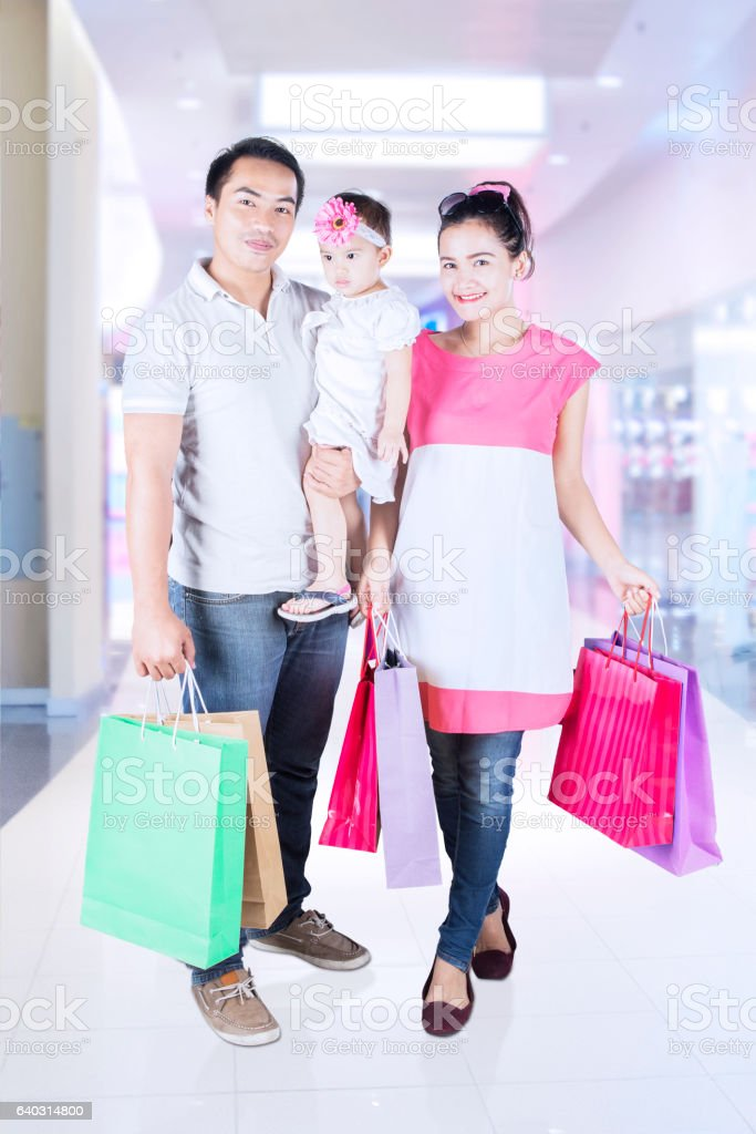 Happy parents and daughter shopping together stock photo