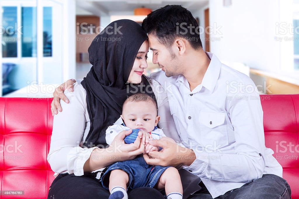Happy parents and their son on the sofa stock photo