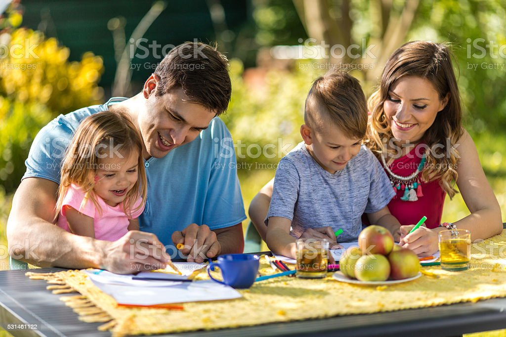 Happy parents coloring with their children in nature. stock photo