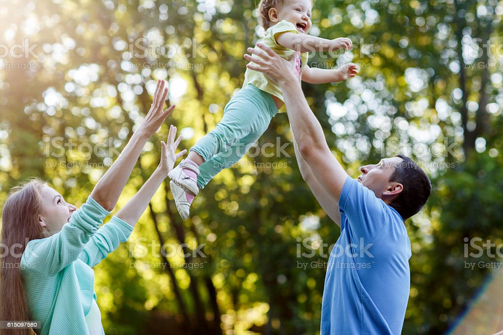 Happy parents enclose ittle girl in park stock photo