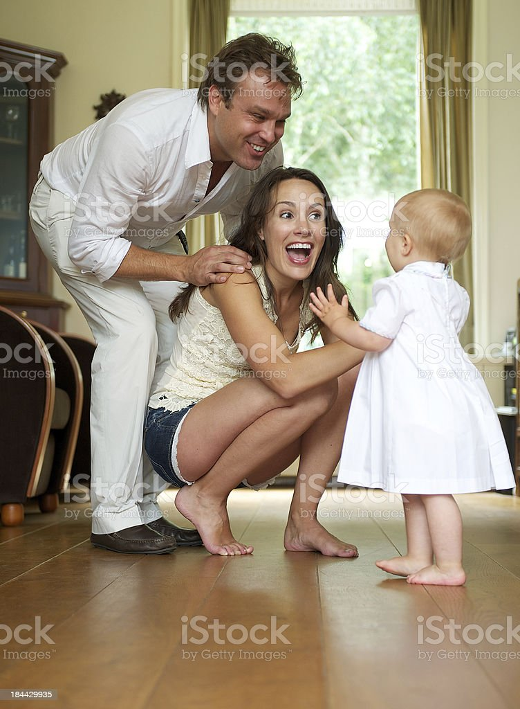 Happy parents helping baby take first steps stock photo