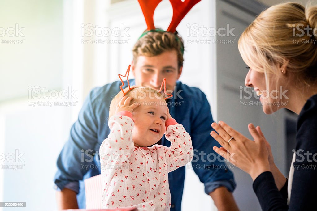 Happy parents looking at baby wearing Christmas headband stock photo