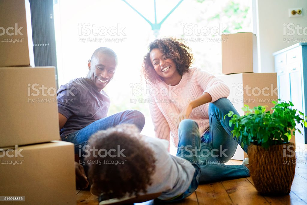 Happy parents looking at son in new house stock photo