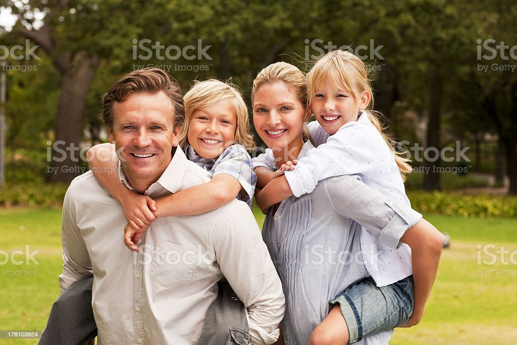 Happy parents piggybacking their children at park royalty-free stock photo