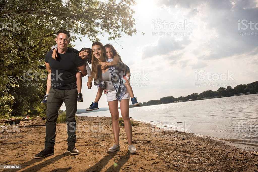 Happy parents piggybacking their children near the river. stock photo
