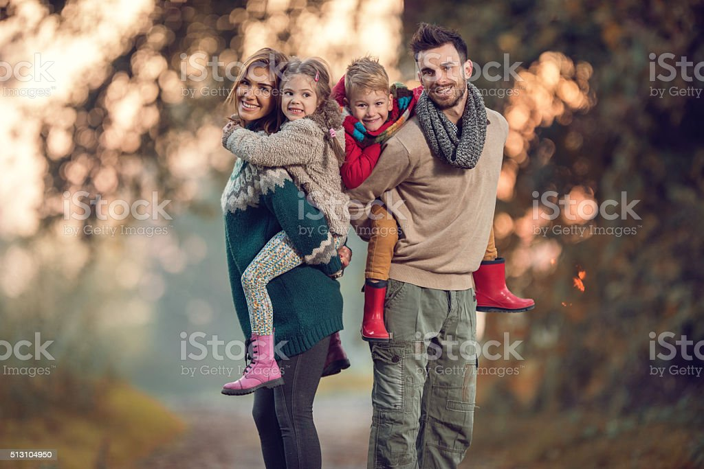 Happy parents piggybacking their small children in the park. stock photo