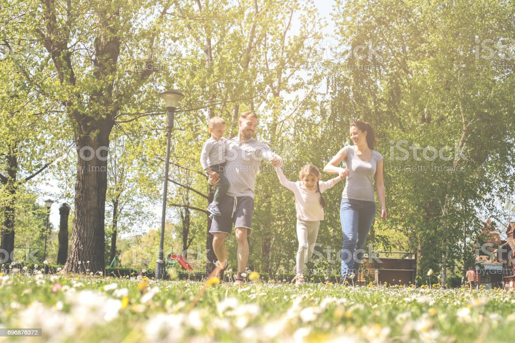 Happy parents playing with their children in the meadow. Family having fun in the spring day. stock photo