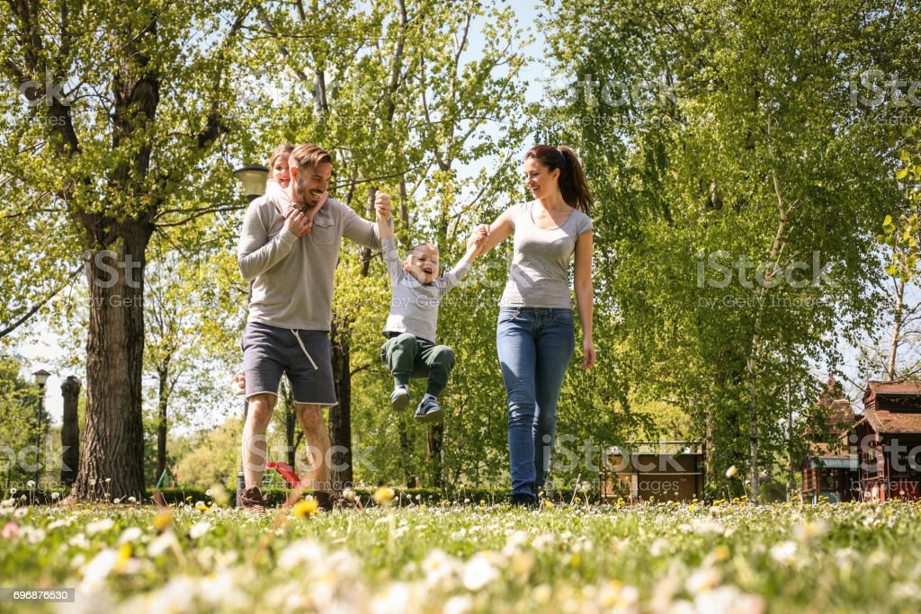 Happy parents playing with their children in the meadow. Family having fun in the spring day. Father carrying her little girl on piggyback. stock photo