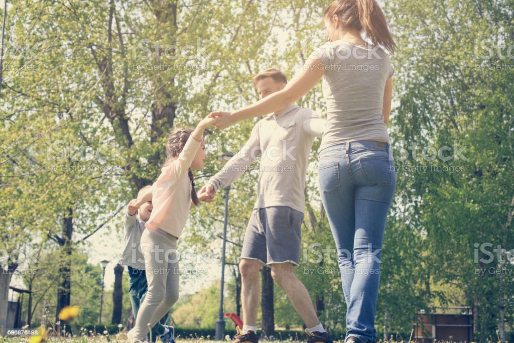 Happy parents playing with their children in the meadow. Family in meadow holding hands and spinning in circle. stock photo