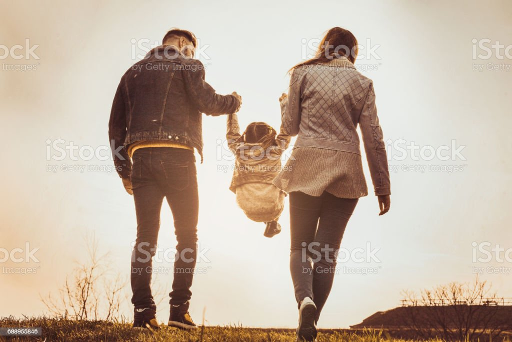 Happy parents playing with their daughter in the park. Parents raise in the air a little girl. stock photo