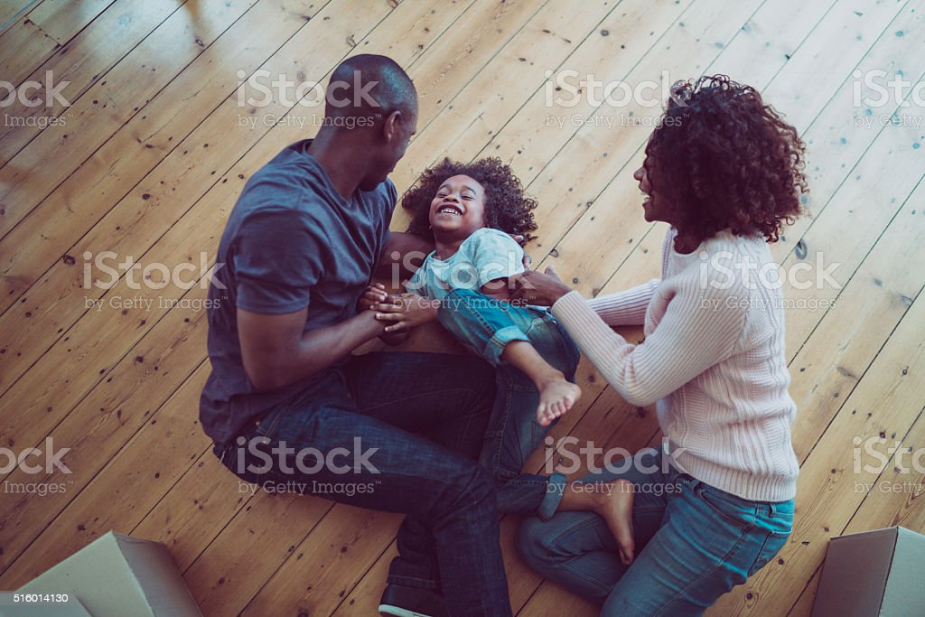 Happy parents tickling son on hardwood floor stock photo