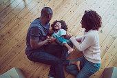 Happy parents tickling son on hardwood floor