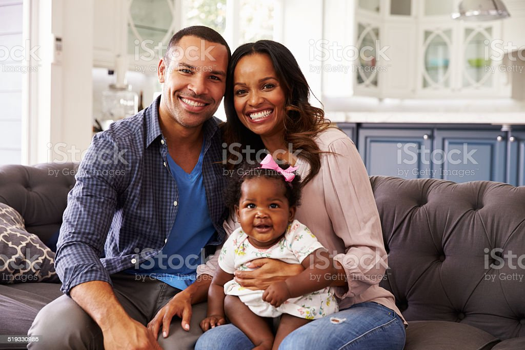 Happy parents with a baby girl sitting on mum's knee stock photo