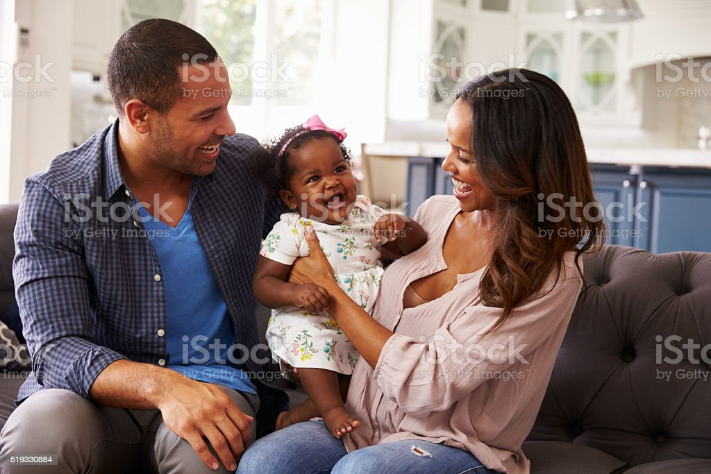 Happy parents with baby girl standing on mum's knee stock photo