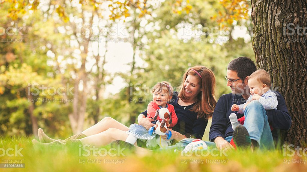 Happy parents with children outdoors having a good family time stock photo