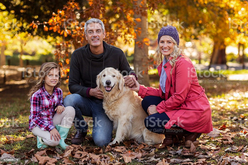 Happy parents with daughter and dog at park stock photo