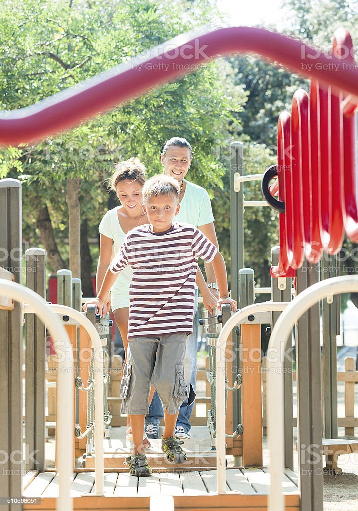 Happy parents with teenage son overcomes the obstacle course stock photo