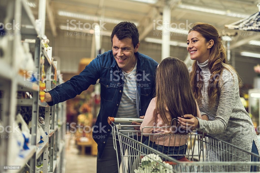 Happy parents with their child shopping in the store. stock photo